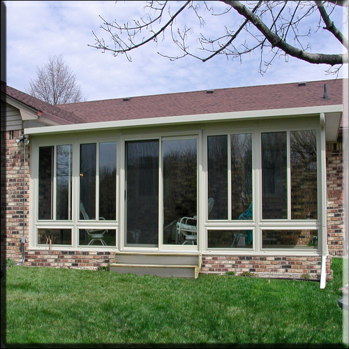 Studio-style composite sunroom w/ brick foundation and deck/patio